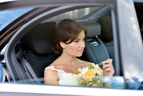 63524633 - beauty bride in bridal gown with bouquet and lace veil in the car.