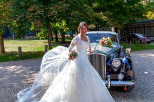the bride next to the wedding car